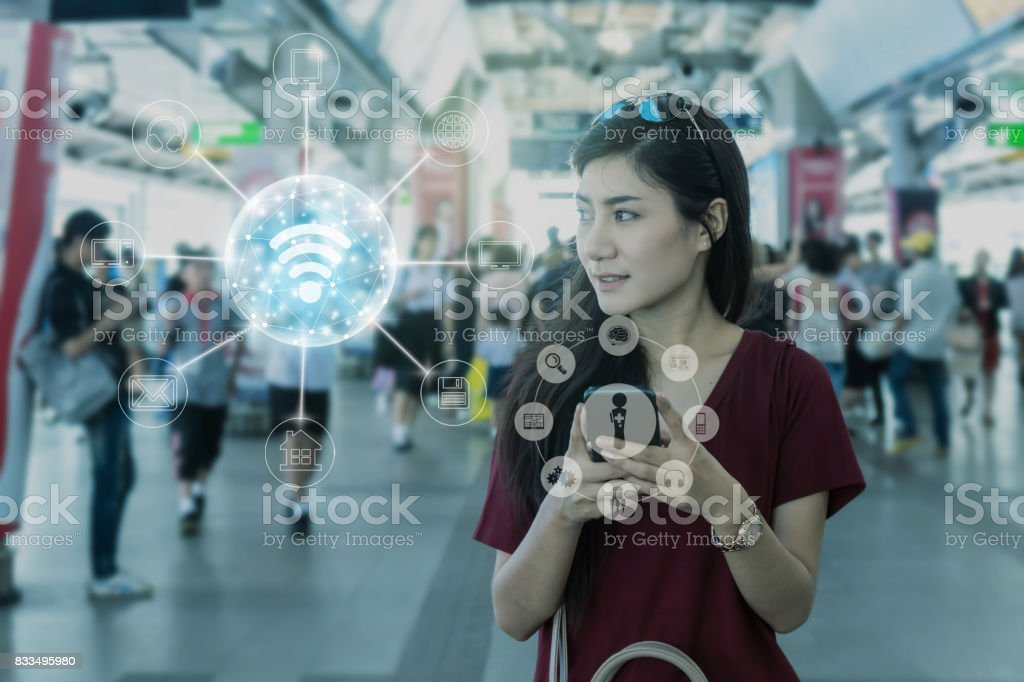 Asian woman passenger with casual suit using the smart mobile phone in the BTS Skytrain rails or MRT subway for travel and online shopping with omni channel, lifestyle and transportation concept stock photo