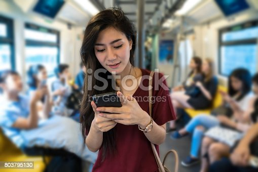 Asian woman passenger with casual suit using the social network via smart mobile phone in the BTS Skytrain rails or MRT subway for travel in the big city, lifestyle and transportation concept