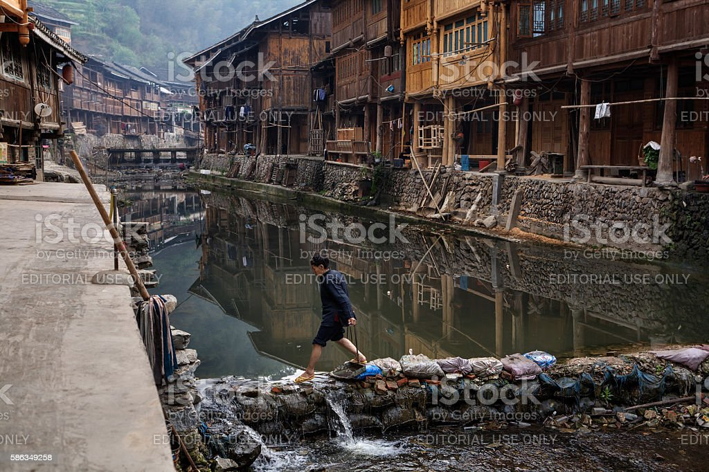 Asian woman passes countryside river on stones of dam, China. stock photo