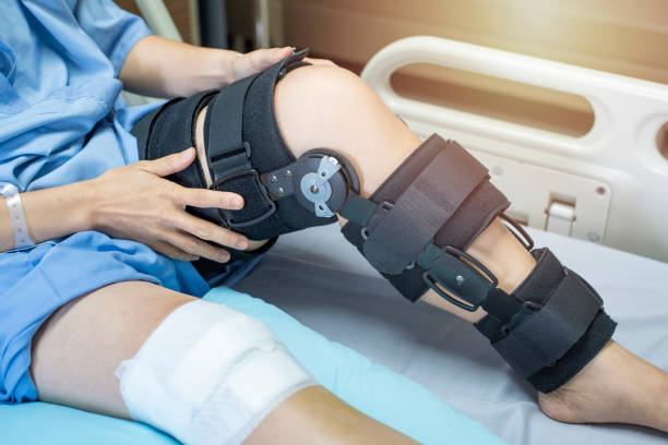 asian woman patient with bandage compression knee brace support injury on the bed in nursing hospital.healthcare and medical support. - spina dorsale umana foto e immagini stock