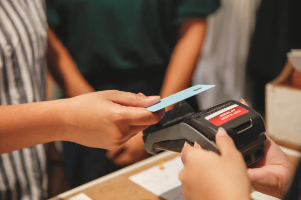 Asian woman paying with contactless card payment to prevent Covid 19 spreading stock photo