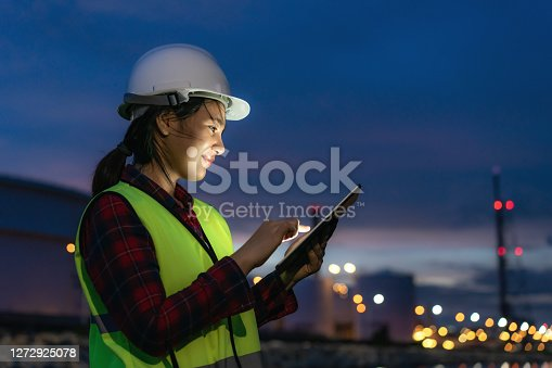istock Asian woman petrochemical engineer working at night with digital tablet Inside oil and gas refinery plant industry factory at night for inspector safety quality control. 1272925078