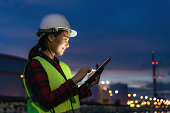 Asian woman petrochemical engineer working at night with digital tablet Inside oil and gas refinery plant industry factory at night for inspector safety quality control.\
