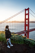 Asian woman photographer and tourist enjoy looking at Golden Gate Bridge during sunrise, Iconic bridge and famous landmark of San Francisco, California, USA. Travel photography concept