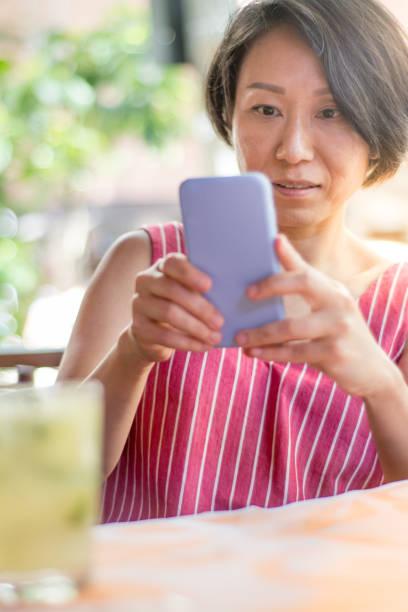 スマートフォンで飲み物を撮影するアジアの女性 - showus ストックフォトと画像