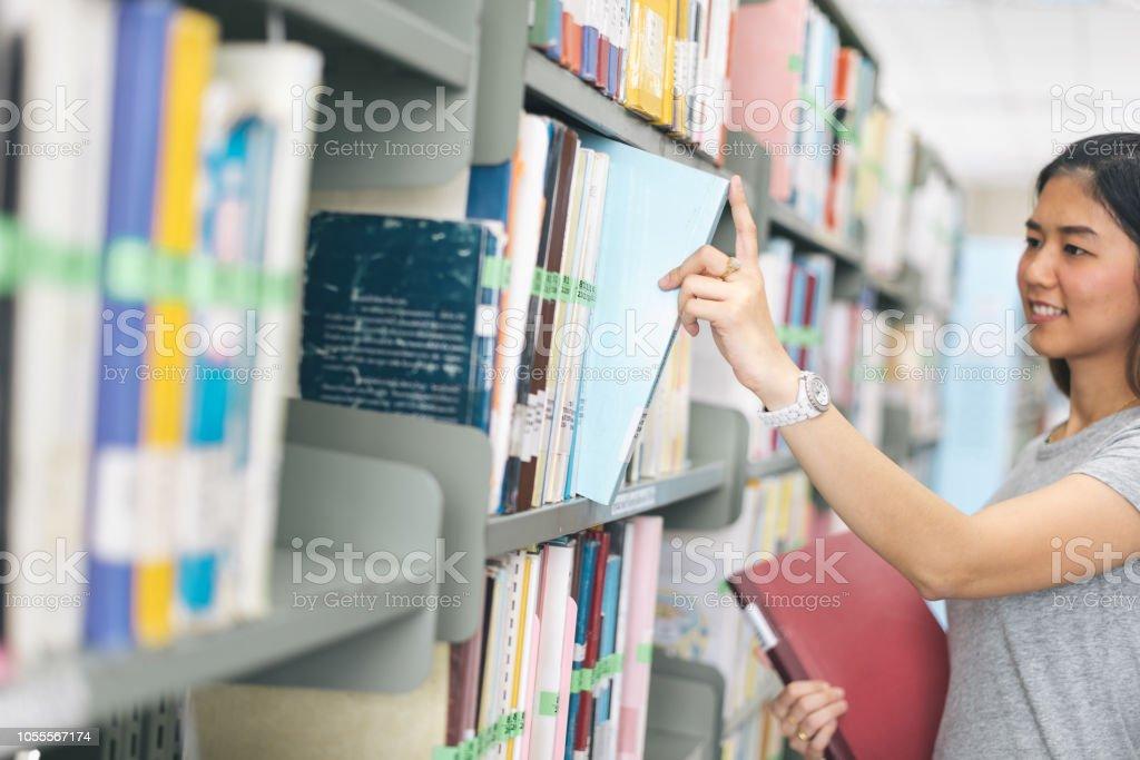 Asyalı kadın. kütüphanede bir kitaptan bir kitaplık seçmek