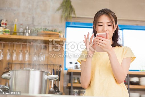young attractive asian woman who cooks while using a smart phone