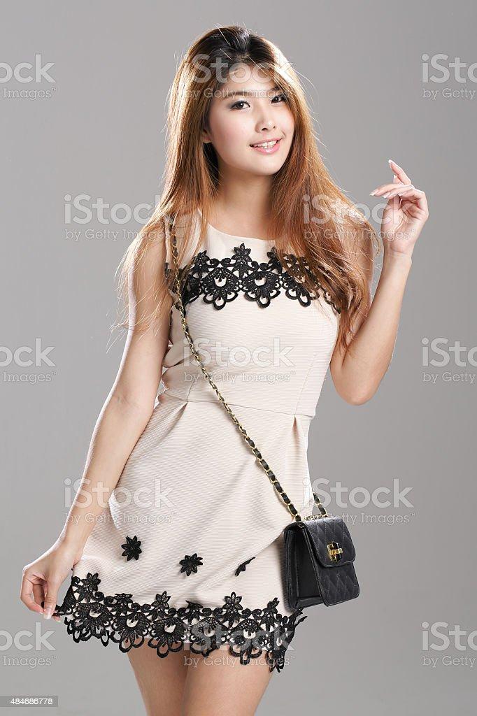 Asian woman Pleated Sleeveless Lace Stripe Hem Dress black-sling bag. stock photo
