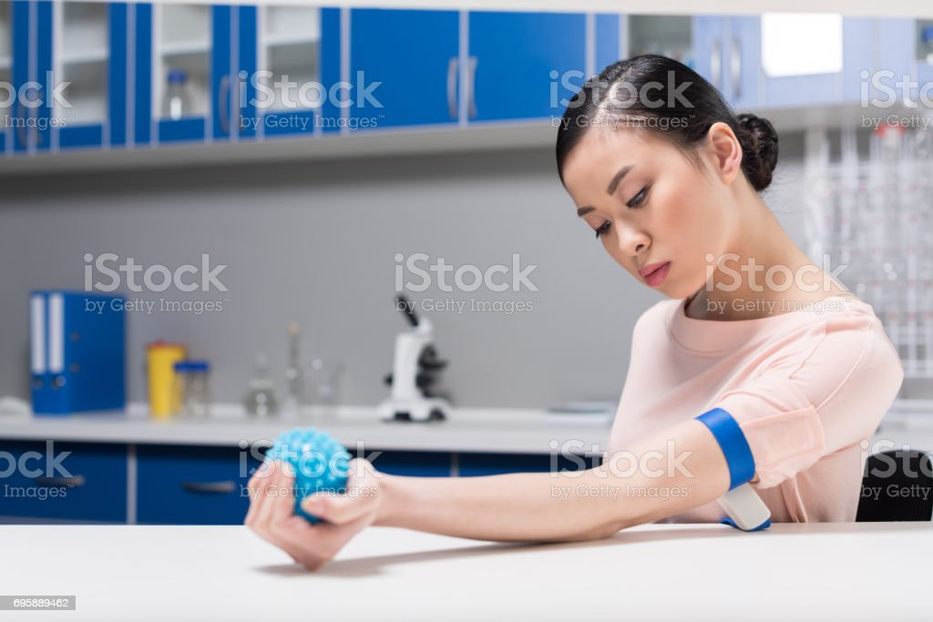 asian woman preparing for blood test by flexing rubber ball stock photo