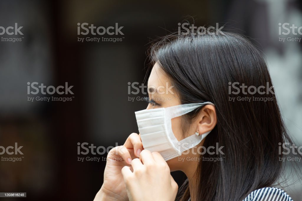 Asian woman putting on face mask Asian woman putting on face mask Adult Stock Photo
