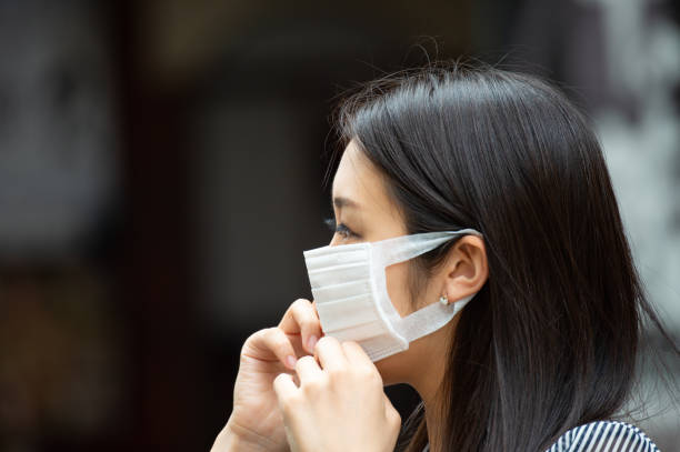 Asian woman putting on face mask - foto stock