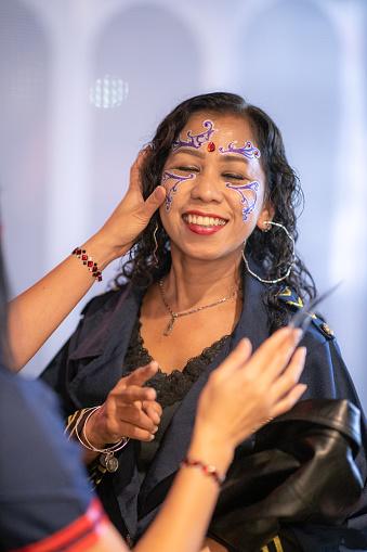 Asian woman putting sticker on face for halloween party