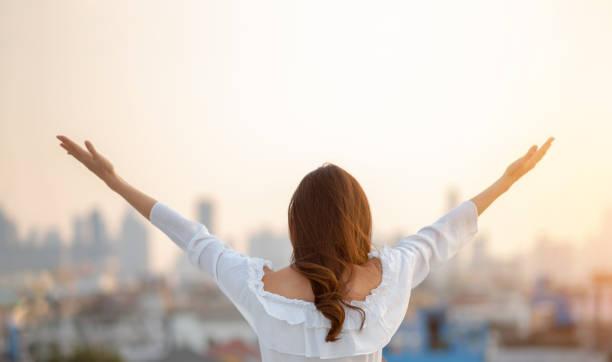 Mujer asiática levantó las manos en el aire sobre el fondo de la ciudad mientras estaba de pie al aire libre. - foto de stock