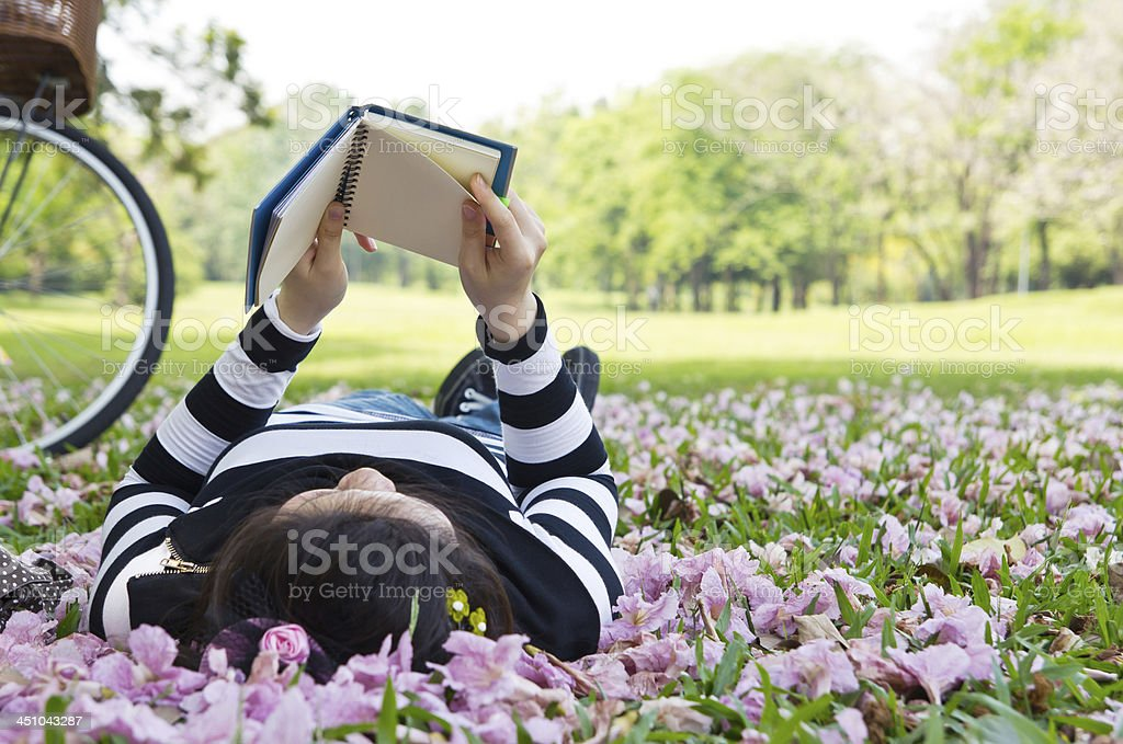 Asian woman reading booklet on the grass stock photo