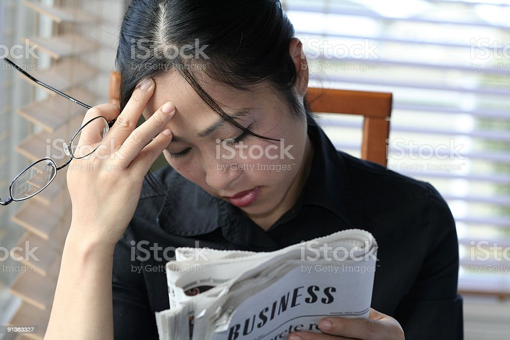 Asian woman reading business section royalty-free stock photo