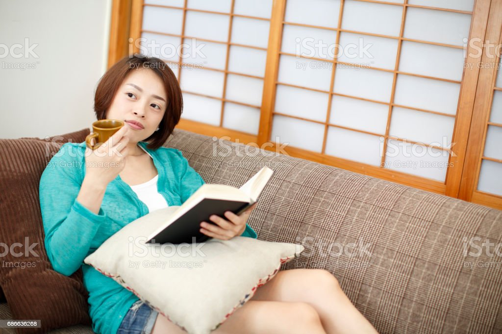 Asian woman reading coffee on the couch royalty-free stock photo