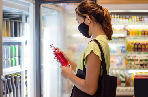 Side shot of a young Southeast Asian woman with face mask reading label of the red soda drinks, standing in front of the supermarket freezer  amidst Covid 19 post pandemic