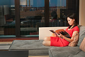 Asian Woman Reading Magazine on Sofa, Inside Apartment at Night
