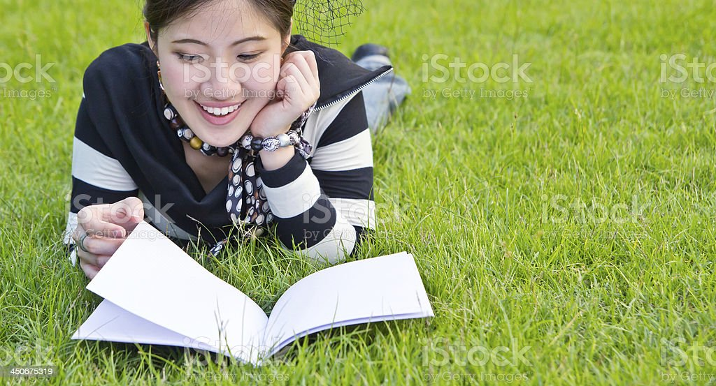 Asian woman reading notebook on the grass stock photo