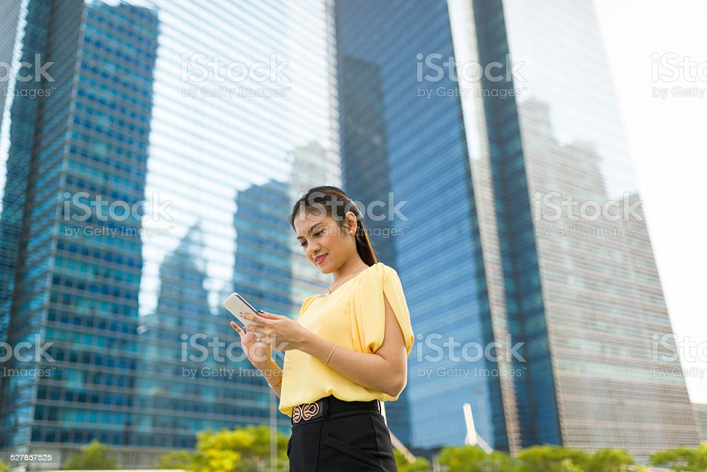 Asian woman reading text messages at outdoor stock photo