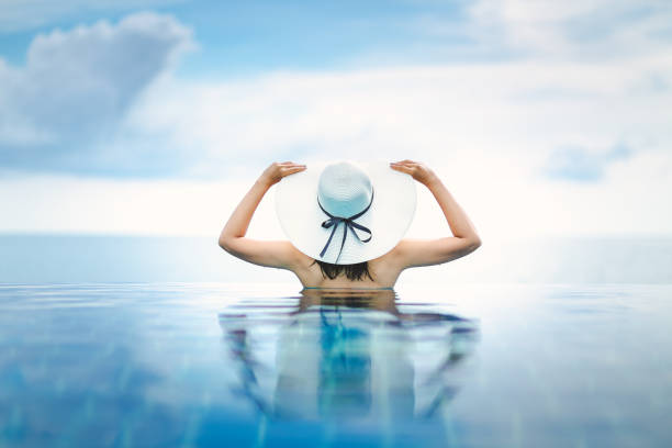 Asian woman relax in pool on beach Summer vacation concept, Asian woman with white hat relax in infinity pool hotel resort with sea beach background at Chanthaburi, Thailand infinity pool stock pictures, royalty-free photos & images