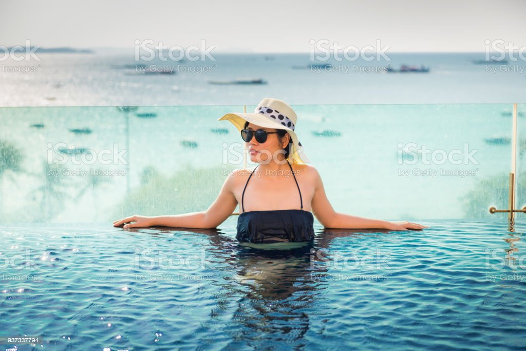 Asian woman relaxing in swimming pool with sunbathe stock photo