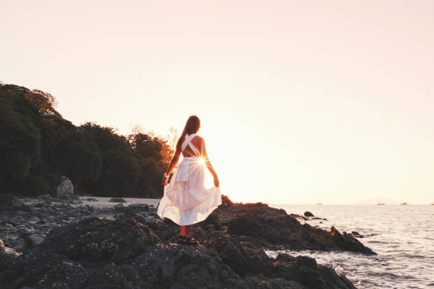 Asian Woman Relaxing near ocean lonely feeling at Sunset time Asian Woman Relaxing near ocean lonely feeling at Sunset time sun shining through dresses stock pictures, royalty-free photos & images