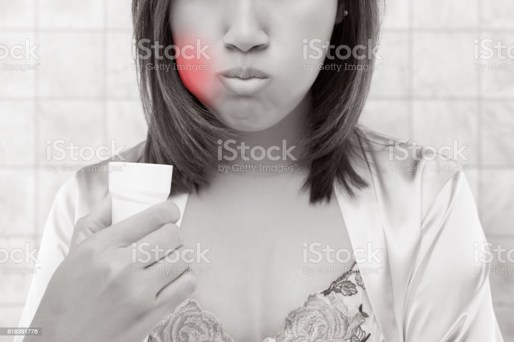 Asian Woman rinsing and gargling while using mouthwash from a glass, During daily oral hygiene routine, Female in a pink silk robe, Dental Healthcare Concepts stock photo
