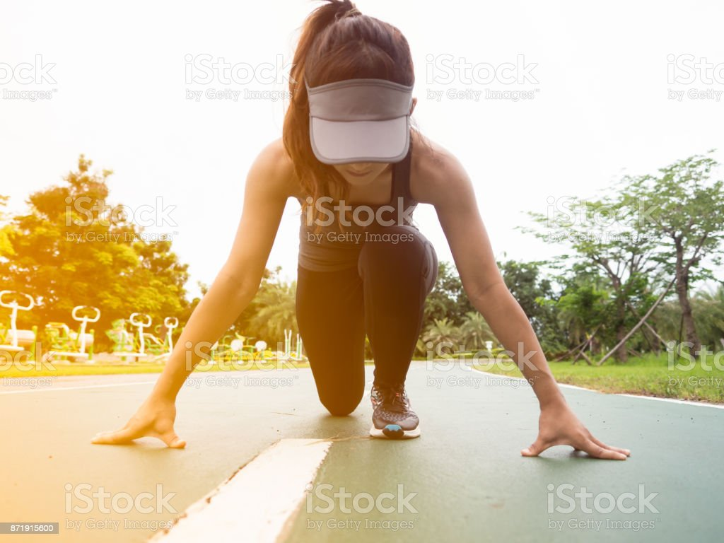 Asian woman runner getting started to run at a park in a morning stock photo