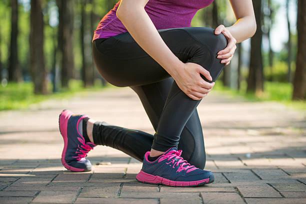 Asian woman runner hold Knee Pain ,Human Leg stock photo