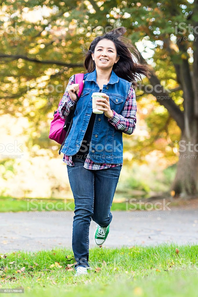 Asian woman running holding a cup of coffee and backpack stock photo