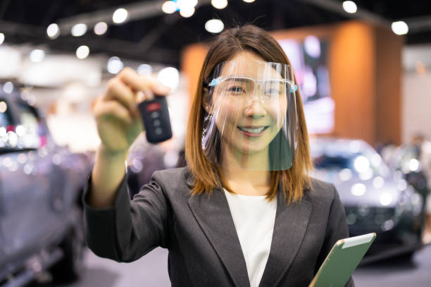 Asian woman saleperson selling new car stock photo