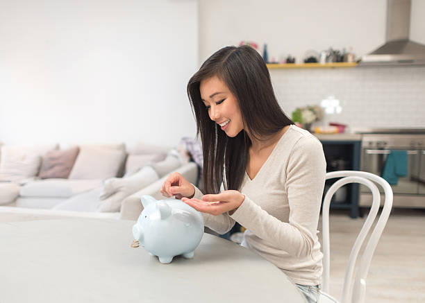 Asian woman saving money in a piggybank stock photo