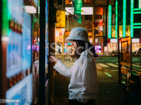 Asian woman paying with smartphone to vending machine.