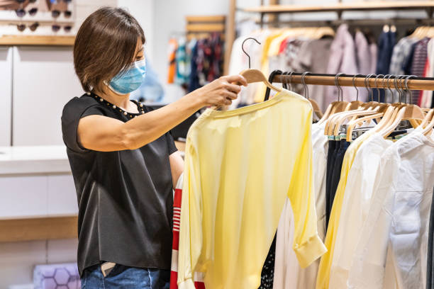 Asian woman shopping apparels in clothing boutique with protective face mask as new normal requirement stock photo