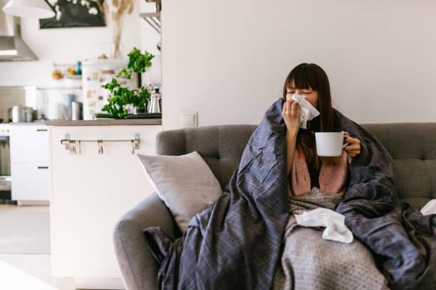 アジアの女性病気自宅で共通の風邪 - くしゃみ 日本人 ストックフォトと画像
