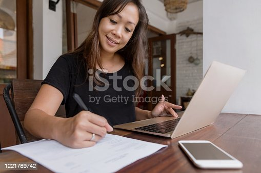 Portrait shot of business woman signing new business contract at home, amidst Coronavirus pandemic