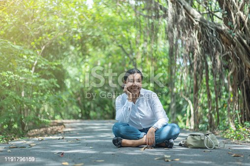 istock Asian woman sit and smile on the road in the garden. Black hair and white t-shirt 1191796159
