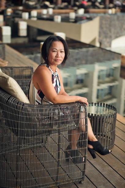 asiatische frau sitzen auf der terrasse - hofkleider stock-fotos und bilder