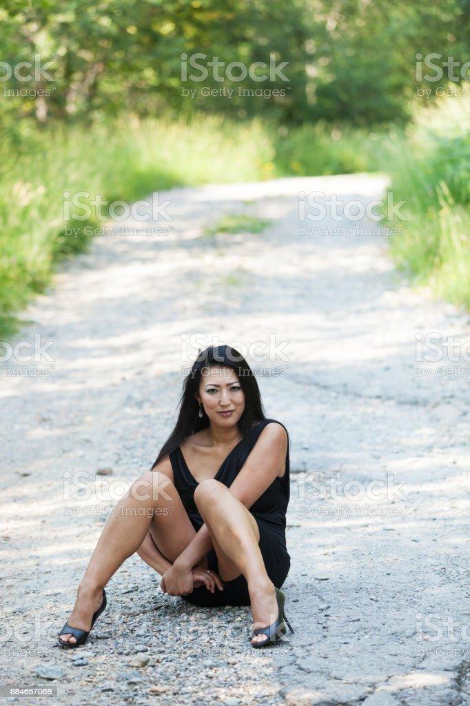 Asian woman sitting cross-legged in the street stock photo