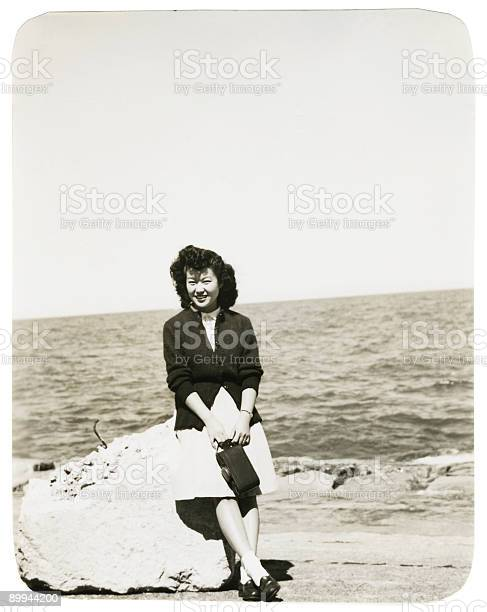 Asian Woman Sitting on a Rock at the Beach