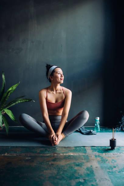 mulher asiática sentada em um tapete de exercício e aquecendo-se para uma sessão de yoga - meditation - fotografias e filmes do acervo