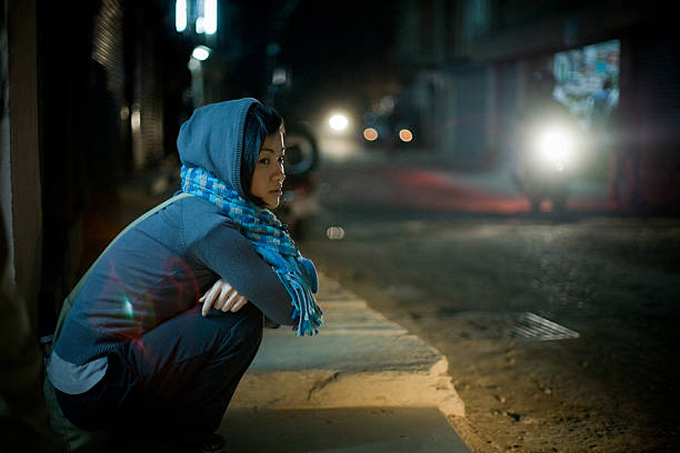 Asian woman sitting on street at night stock photo