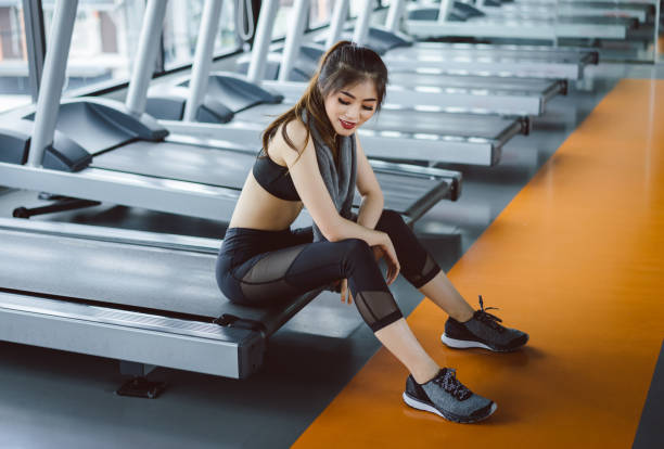 asian woman sitting on treadmill after workout or running exercise for muscle at fitness gym healthy lifestyle bodybuilding - runner rehab gym foto e immagini stock