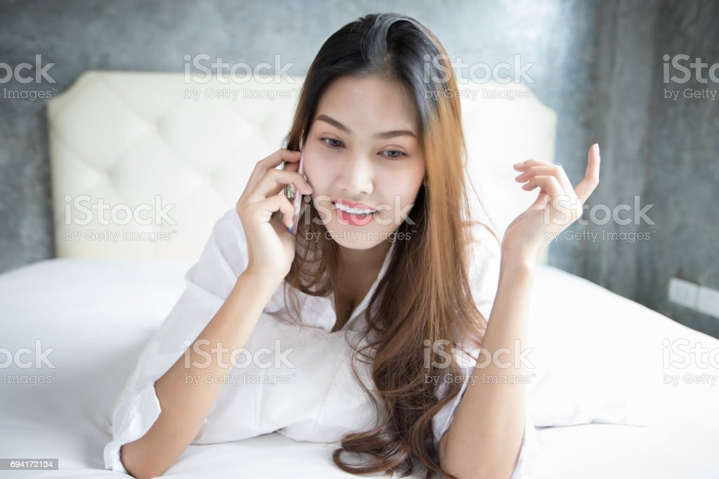 Asian woman Smile feel carefree and she lying on the bed in the morning and  young beautiful girl will using smartphone for call - Stock image .