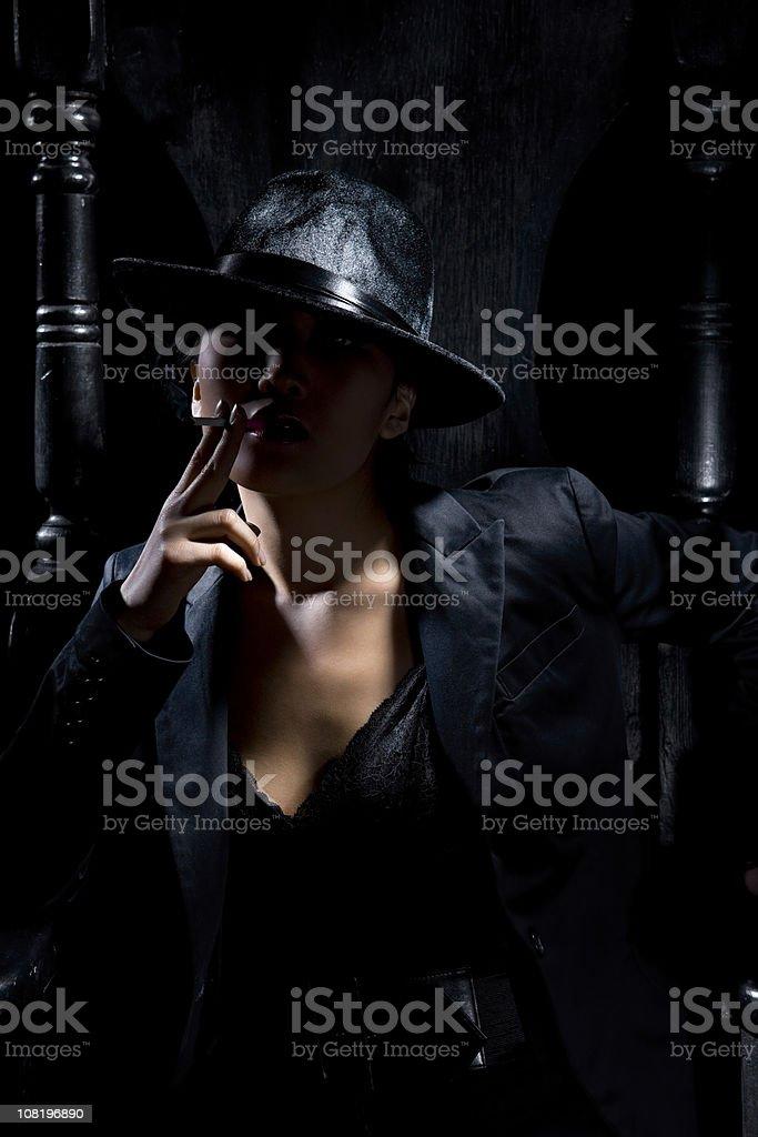 Asian Woman Smoking Cigarette, Posing as Gangster in Black royalty-free stock photo