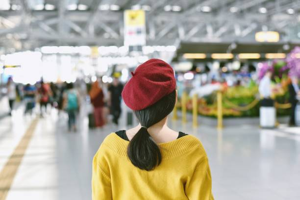 Asian woman standing in trade fair exhibition hall, Blurred background of large crowded people at big event with copyspace. stock photo