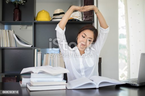 istock Asian woman stretching at her workplace and smiling in the office 668090816