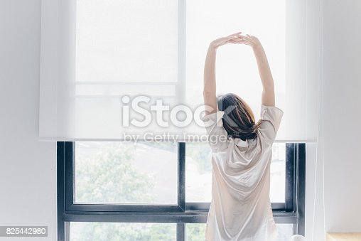 istock Asian woman stretching near the window after her wake up in the morning, back view. 825442980