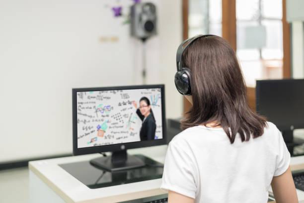 亞洲女學生視訊會議與老師在大學機房的電腦上的電子學習。電子學習、 線上,教育理念。圖像檔